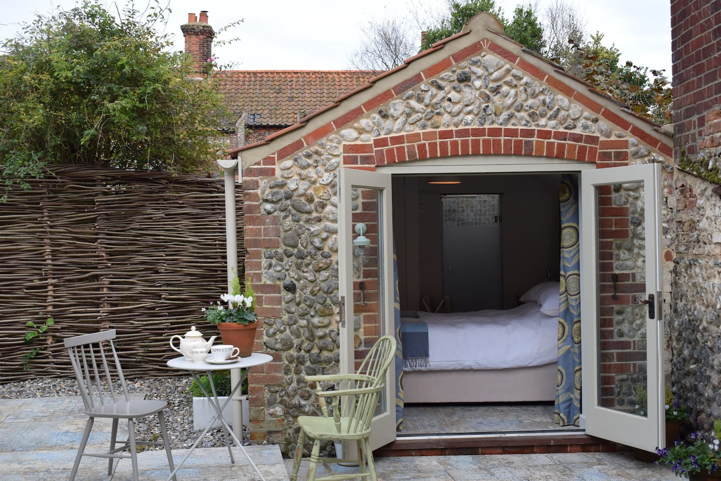Open French doors on a sunny day with table and seating to enjoy the garden and have a drink.
