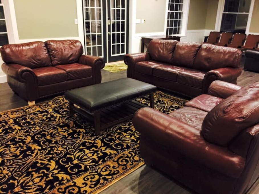 Large spacious living room area with two flat screen TVs and amp social room.