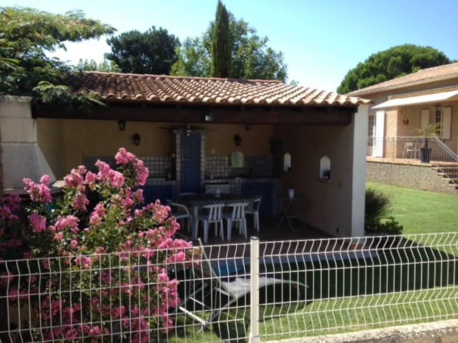 La cuisine d'été, entièrement équipée devant la piscine. En arrière plan, la maison qui donne sur le jardin arboré.