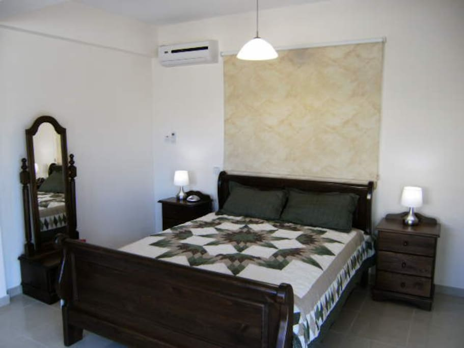 Master bedrom with bedside lamps and dressing mirror.