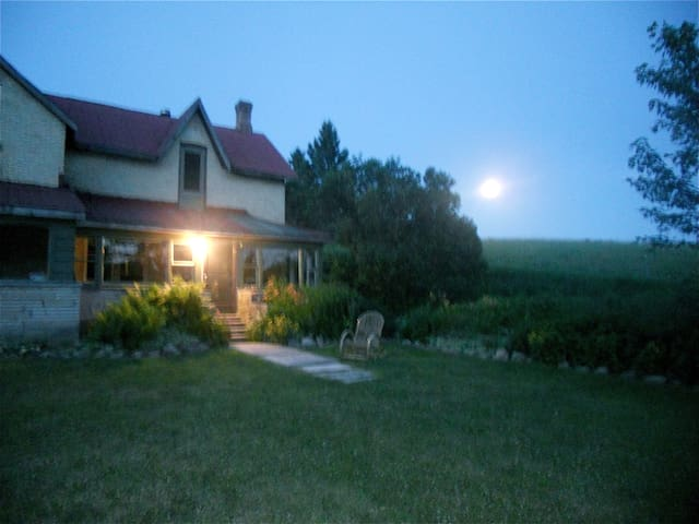 The moon over front hill of the farmhouse.