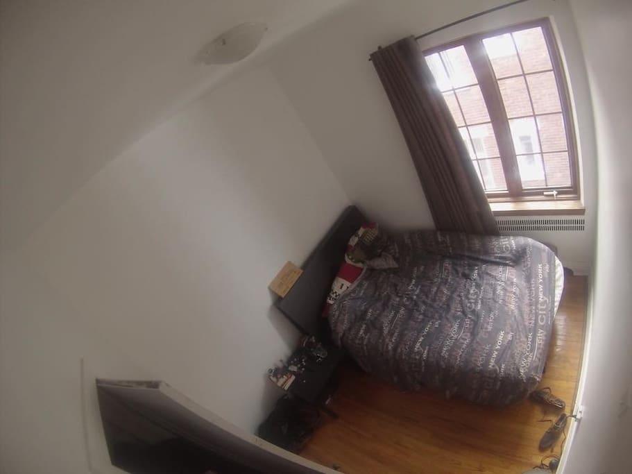 Petite chambre à louer avec un lit double, une table de nuit et un placard