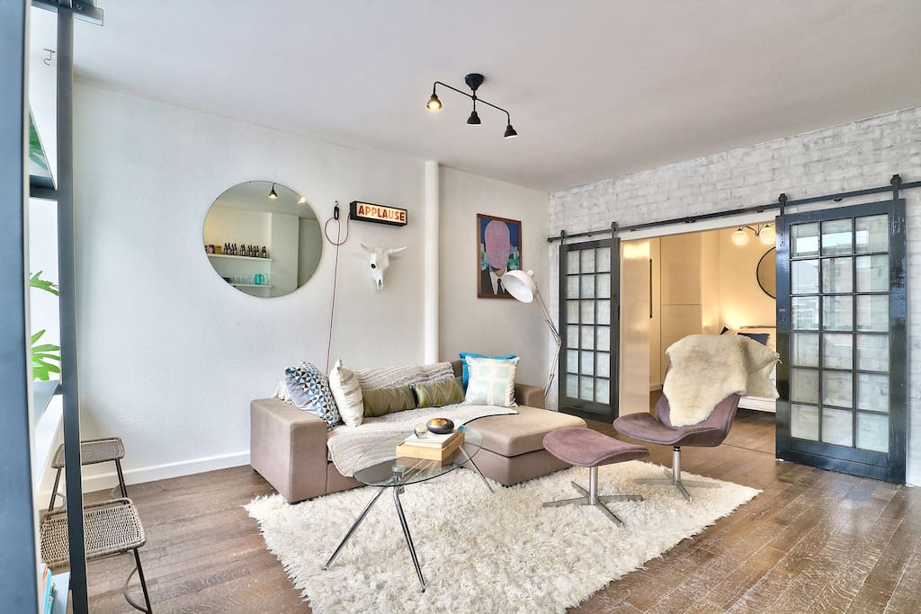 Lounge with L-shaped sofa and swivel chair, dark oak wood floors