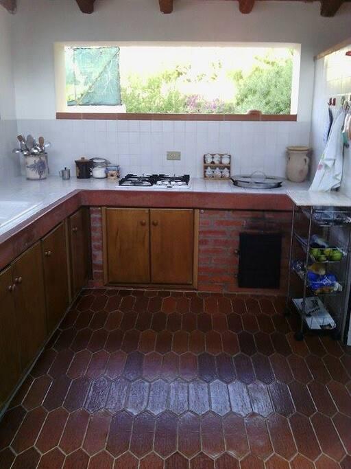 Cucina all'esterno munita di fornelli a gas e forno a legna