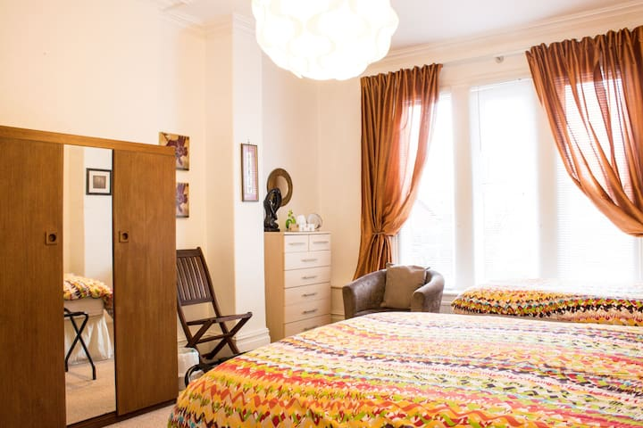 This much larger bedroom (19') has a double bed and two singles. There are bedside cabinets and small lamps and there is a hairdryer in the large chest of drawers