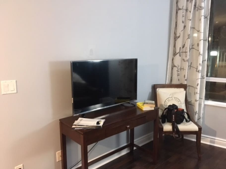 Across from couch at the living room end, 4k TV
