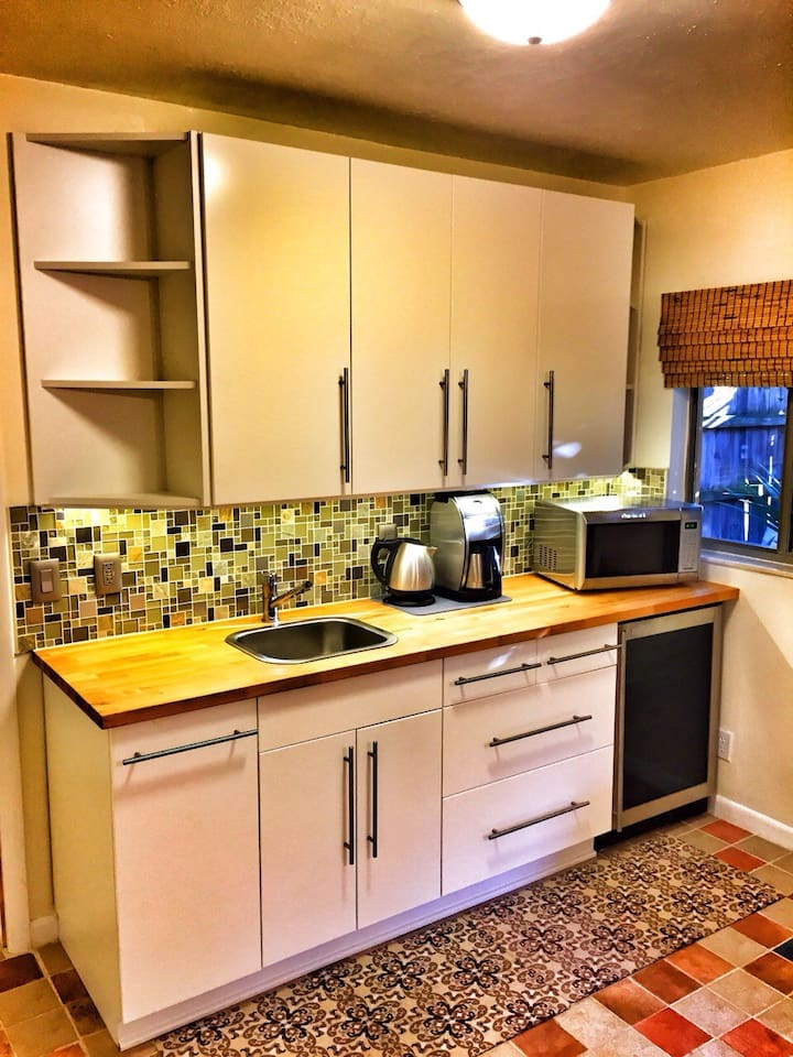 Modern, fully equipped kitchenette with fridge, coffee pot and tea kettle