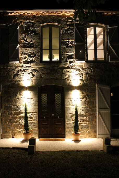 The west facade and tree lined front door to Le Manoir illuminated at night