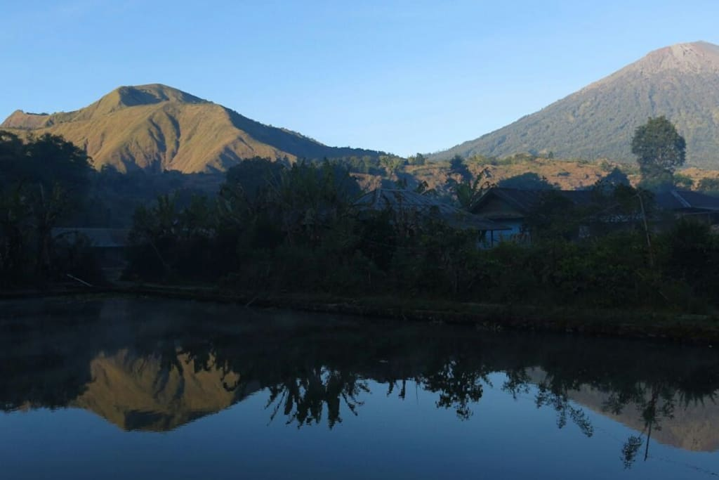The reflection of Rinjani Volcano on pond near the house