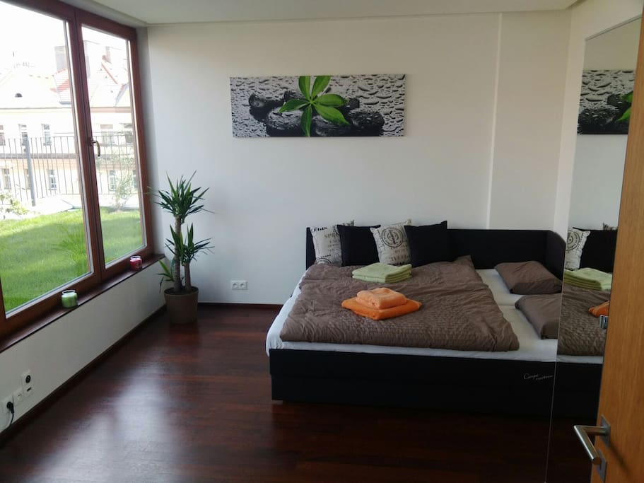 Your private room with comfortable bed for 2 persons and wonderful view on terrace with lawn
