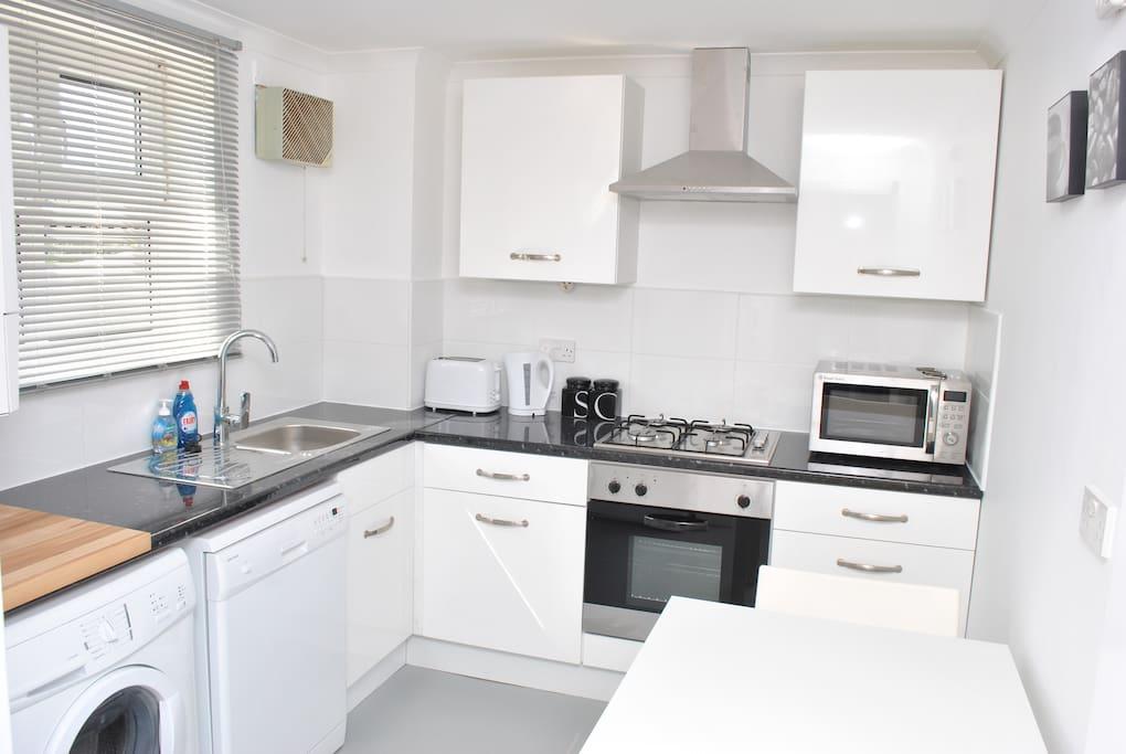 Modern kitchen with dishwasher, microwave, washing machine and fridge freezer