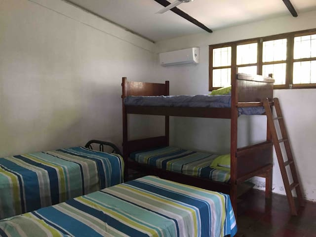 Room #2, has 2 twin beds and a bunk bed and a full bathroom.