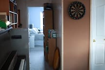 Dartboard in open area and hallway leading to the bedrooms and bathroom.