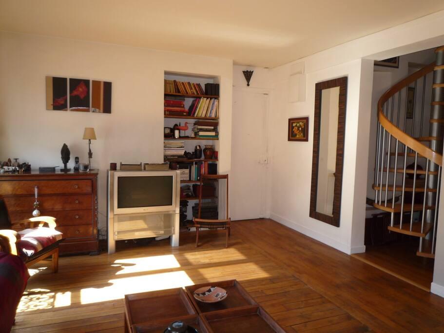 Partie droite du salon avec vue sur escalier d'accès aux chambres