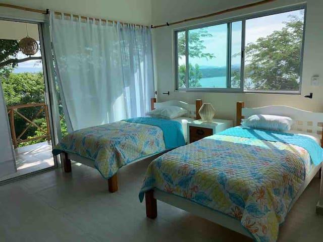Dos camas individuales en el salón de la planta alta con acceso al balcón y vista al lago.