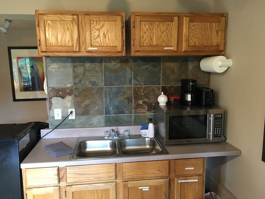 Kitchenette with refrigerator/freezer, microwave, coffee and coffee maker.