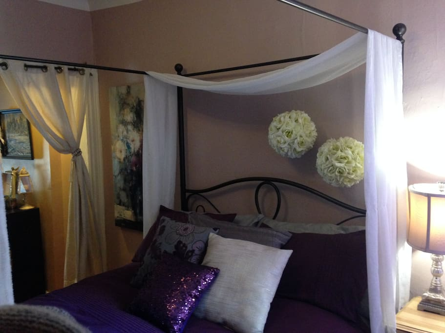 canopy queen sized bed.  Curtain separating bedroom from living room.