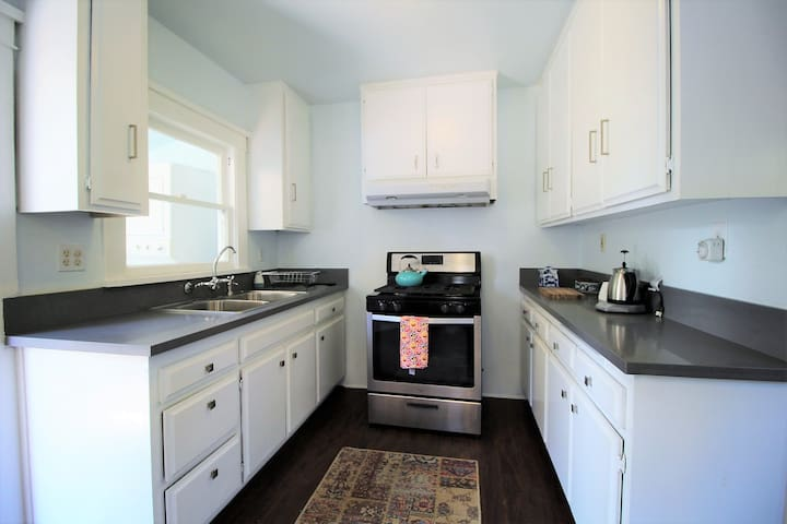 Good size kitchen, quartz countertops, stainless appliance, and full size refrigerator.  All the cooking supplies you need