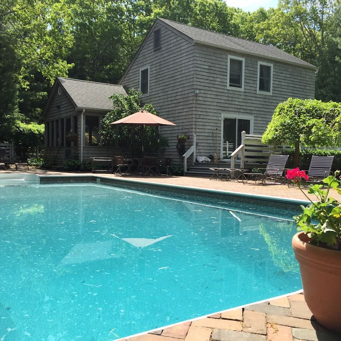 20x40 heated pool with brick paving surround. Enclosed deck and deck with grill off of the kitchen are pictured. There are many Brown Jordan lounge chairs and an outdoor dining table.