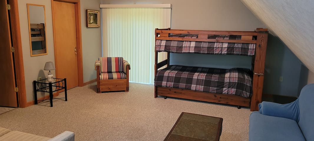 Loft twin-size bunk beds with an additional twin-size trundle bed stored underneath.
