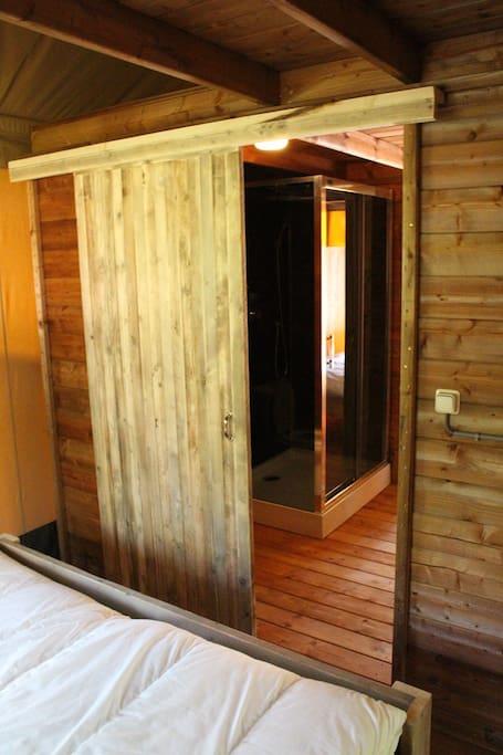 Badkamer met douche, toilet en wasmeubel.