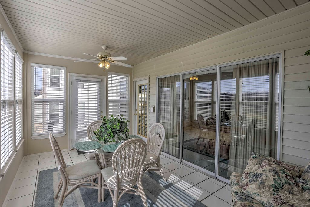 Enjoy early mornings in the sunroom overlooking the green, wooded golf course.