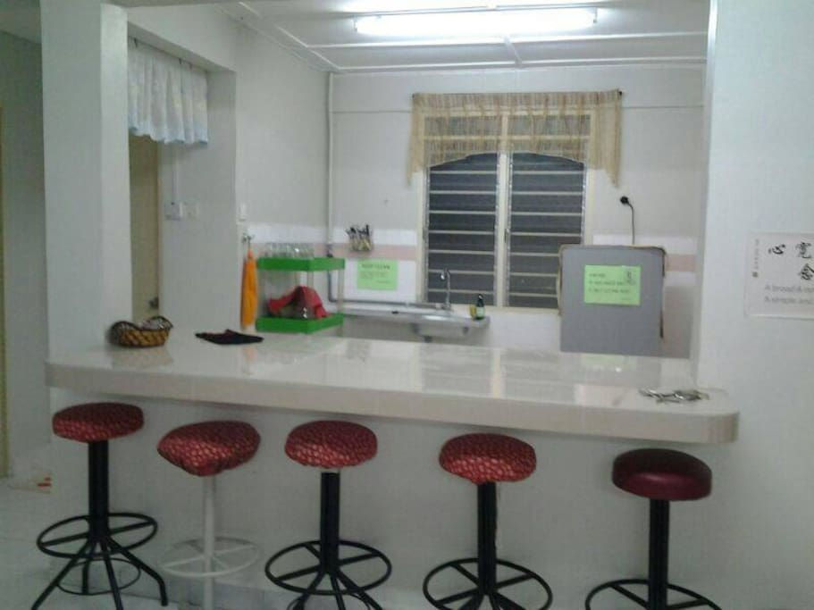 Kitchen with kettle, fridge and dining place.