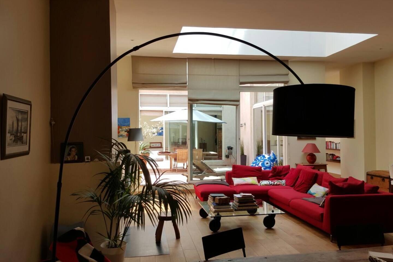 Séjour avec une large ouverture au plafond de la verrière offrant lumière zénithale