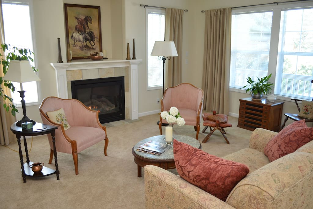 Relax in the comfortable living room, featuring abundant natural light and cozy seating around the gas fireplace.