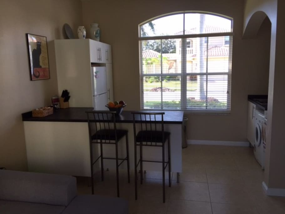 fully stocked kitchen with eat-at countertop, microwave, refrigerator/freezer, stove & all-in-one washer dryer