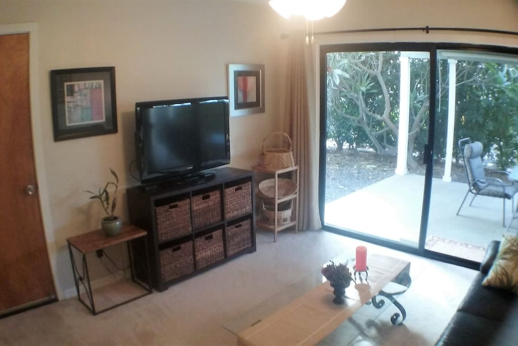 sitting room with flat panel TV and glass sliding door to patio