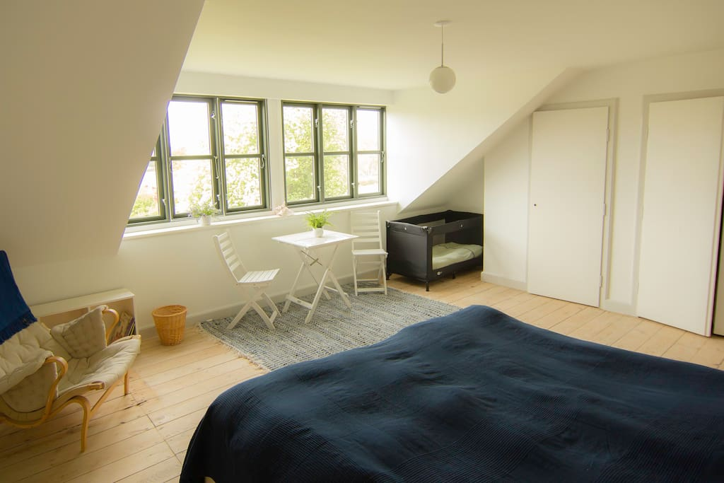 Huge window with view, baby bed, table and chairs, arm chair.