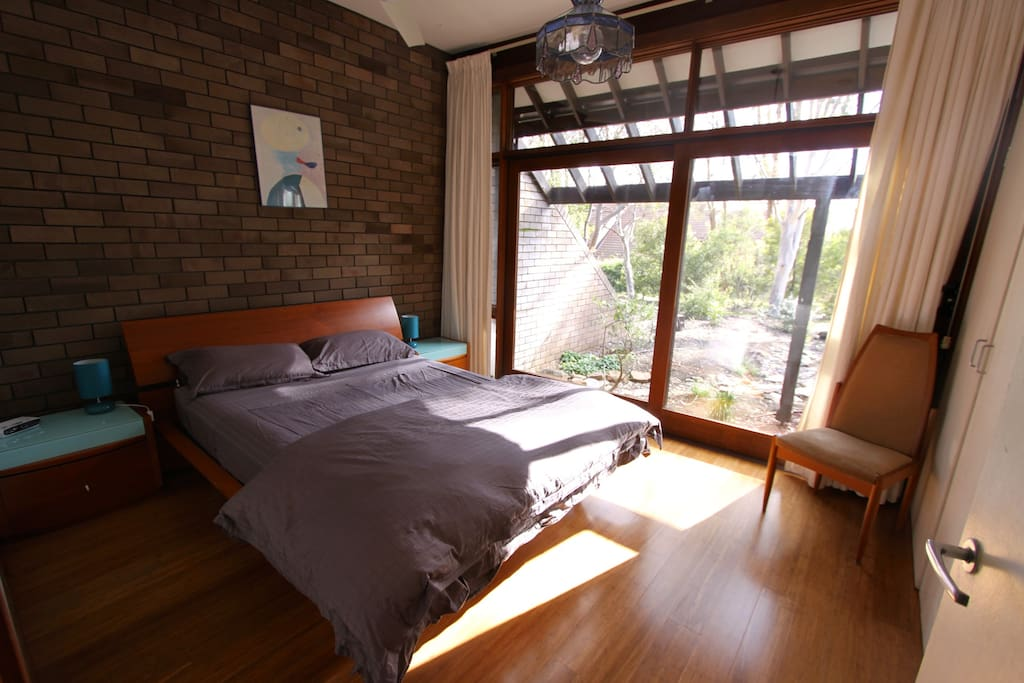 Master bedroom with 3m high ceilings and full northern windows overlooking courtyard.