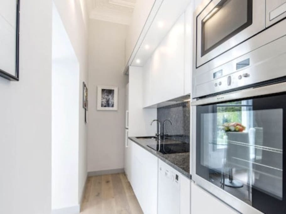 Open plan kitchen with sink, tall fridge/freezer, 1 oven, 1 microwave, dishwasher, kettle, toaster
