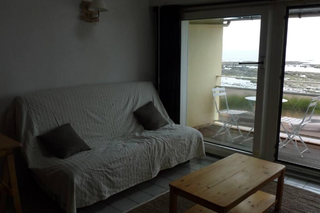 Salon avec canapé-lit 2 places face à la mer