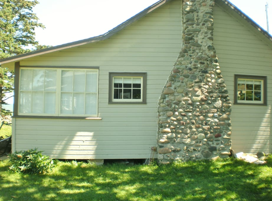 A view of the cottage from the lush, green grass in the yard