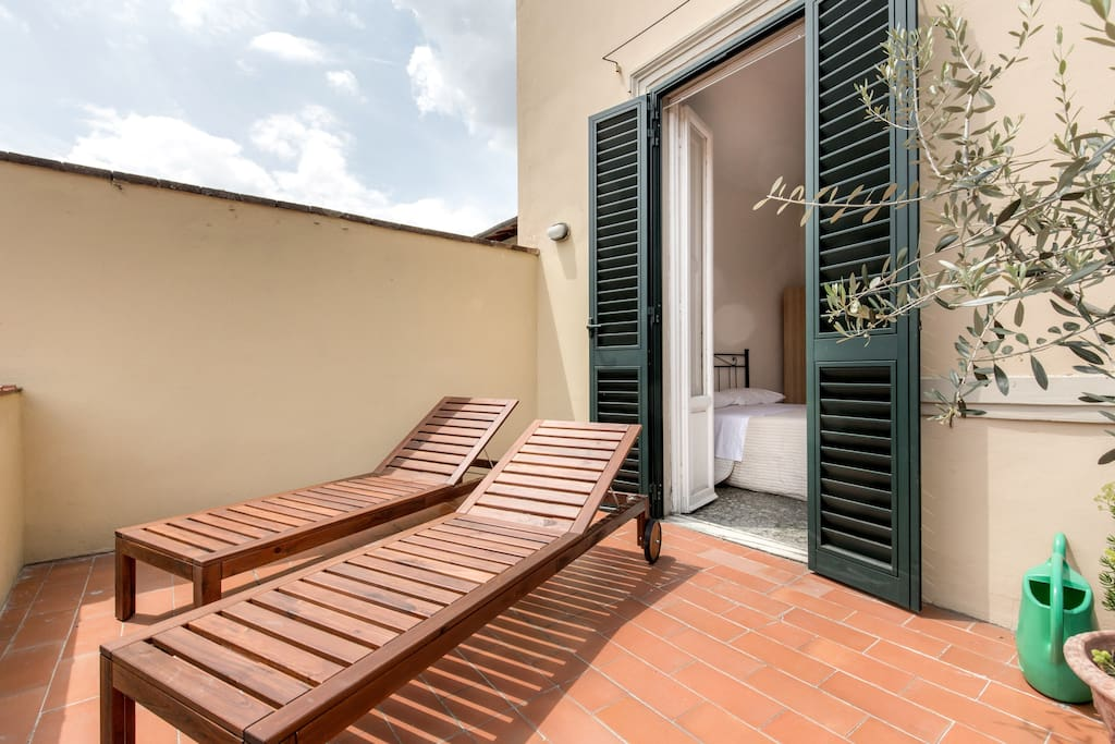 Terrace for Sunbathing of 16m2 with a view of Fiesole and it's hills. 2/3 wooden sunbeds.