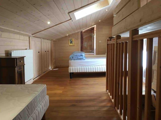 La chambre au 2e étage, avec un lit double (ou 2 lits simples), un autre lit simple (visible sur la gauche), un lit simple supplémentaire en mezzanine (en haut à droite), et au fond une salle de bains