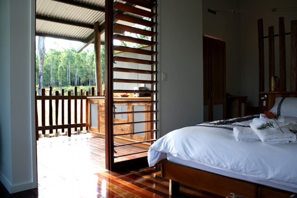 Luxury King size bed looking out to well equipped al fresco kitchen and verandah