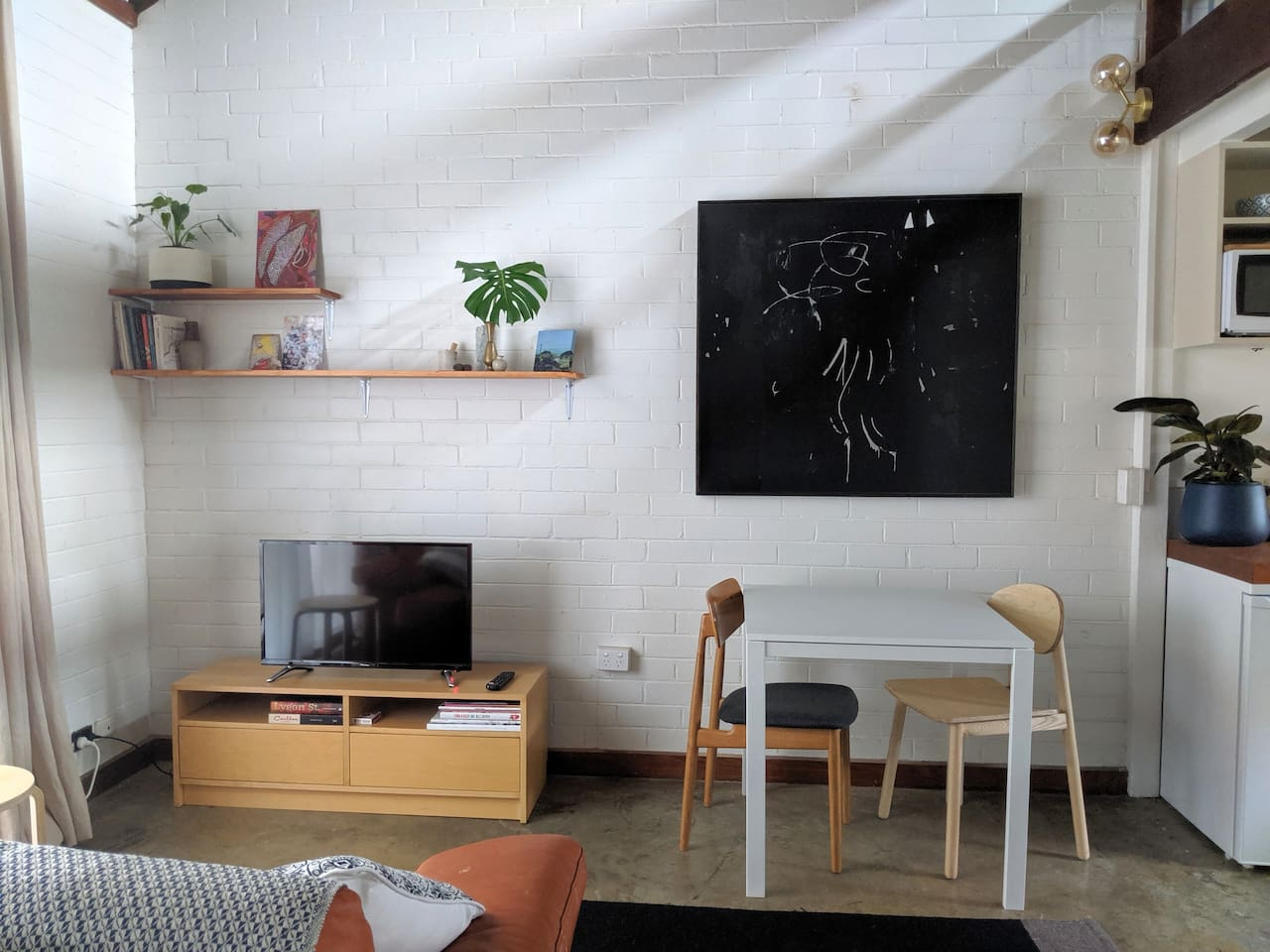 Dining and lounge area featuring artwork by Kathryne Honey, Kate Tucker and Janet De Wagt. Smart TV includes Netflix.