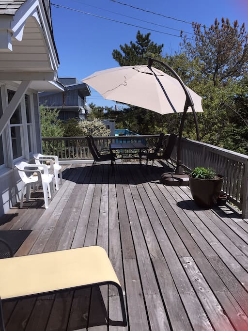 Spacious deck with table, chairs,  lounges, umbrella and outdoor shower