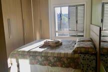 Quarto 1 -  Cama box Queen, roupeiro, espelhos amplos, roupa de cama, travesseiros e toalhas de banho.