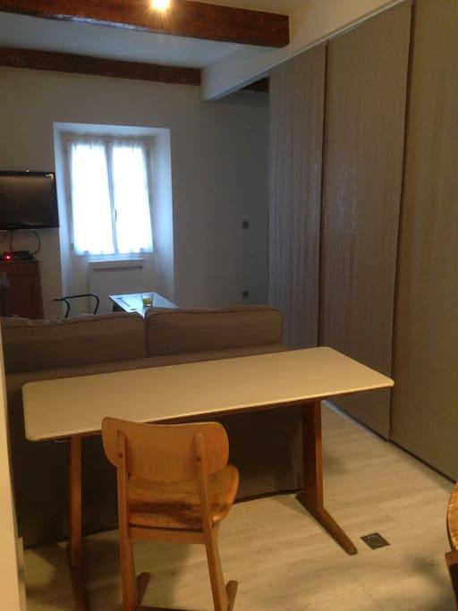 petit bureau avec prise au sol pour ordinateur.Séparation du salon et la chambre par un rideau type japonnais