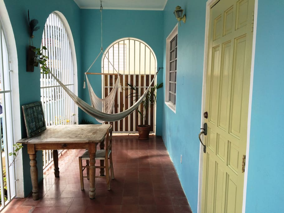 Front balcony: Sunlit relaxing porch with hammocks preempts the entry to the home...