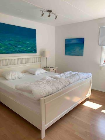 Sovrum 1 på bottenvåningen med dubbelsäng och en barnsäng