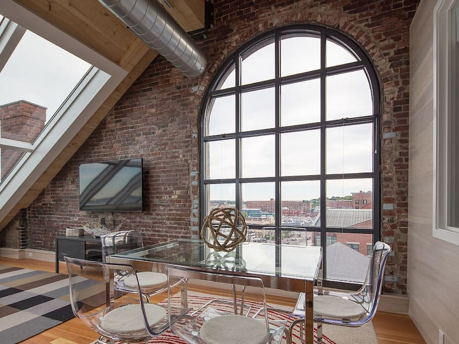 "Dining area with incredible light, exposed brick, and 60"" TV."