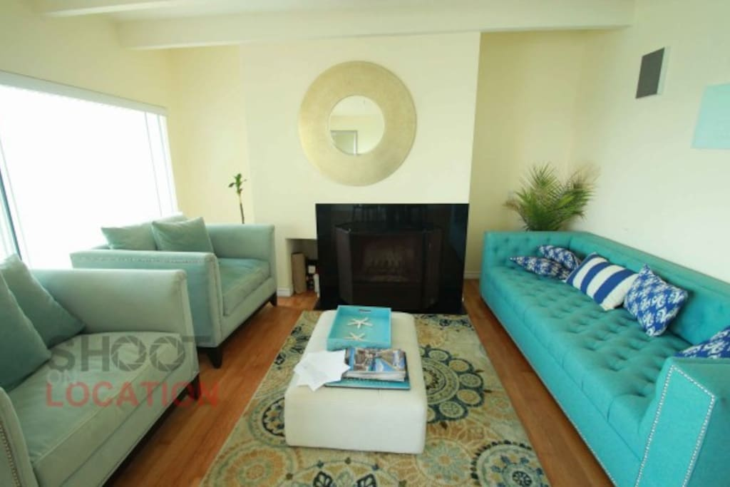 Living room with fireplace and fill view of Pacific Ocean
