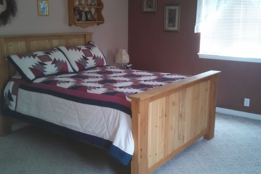 This room features a comfortable queen bed with dresser and chair for sitting. Shared bath.