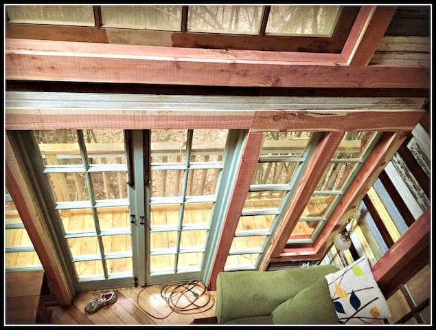 Peering down from the sleeping loft to the wrap around deck through reclaimed Victorian doors and original hardware.