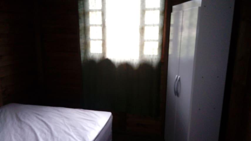 Suíte com cama de casal e armário e ventilador.